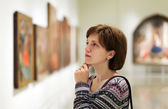 Visitor looking pictures in art gallery — Stock Photo