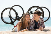 Couple with bikes on beach — Stock Photo
