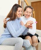 Happy daughter shows pregnancy test — Zdjęcie stockowe