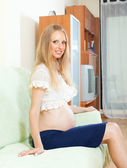 Smiling pregnant woman at home — Stockfoto