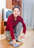 Mature woman polishing parquet floor   — Stock Photo