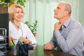 Elderly doctor talking with patient — Stockfoto