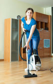 Woman cleans with vacuum cleaner   — Photo