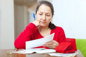 Mature woman reads bills — Stock Photo
