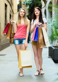Two smiling girls with purchases — Stock Photo