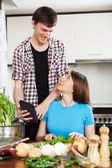 Couple cooking with electronic device — Stock Photo