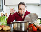 Happy mature woman cooking — Stock Photo