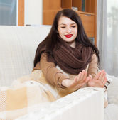 Long-haired woman near electric heater — Stock Photo