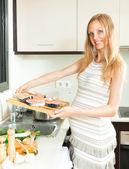 Cute pregnant blond cooks salmon — Stockfoto