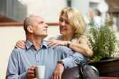 Mature couple on balcony with coffee — Stock Photo