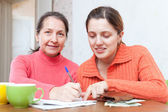 Positive women fills in payments bills — Stock Photo