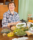 Smiling mature woman with  herbs  — Stock Photo