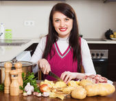 Woman cutting potatoes at table   — Stock Photo