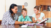 Happy family together doing homework — Stok fotoğraf
