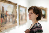 Woman looking pictures in  museum — Stock Photo