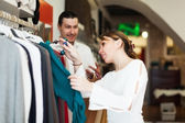 Couple choosing clothes at boutique — Stockfoto