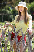 Long-haired woman near fence — Stock Photo