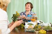 Woman drinking herbal tea with friend — Stock Photo