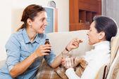 Daughter giving liquid medicament — Zdjęcie stockowe