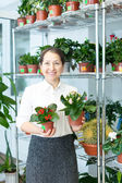 Happy  woman with kalanchoe — Stock Photo