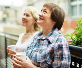 Two women drink tea on balcony — Stock Photo
