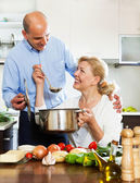 Mature couple cooking in kitchen — Stock Photo