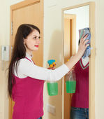 Woman cleaning mirror with cleanser — Stock Photo