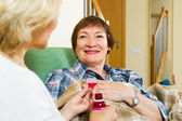 Home employee offering mixture to patient — Stock fotografie