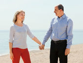 Elderly man and woman holding hands — Stock Photo