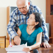 Mature woman fills documents, man helping her — Stock Photo
