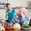 Playing mature couple cooking food — Stock Photo #50778639