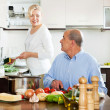 Mature man chopping vegetable and looking at his wife — Stock Photo #50778961