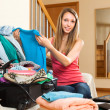 Woman sitting on couch near opened suitcase — Stock Photo #50779203