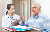 mature doctor talks with  senior man — Stock Photo