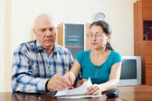 Serious mature couple fills in questionnaire  — Stock Photo
