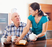 Woman serving toast to  husband — Stock Photo
