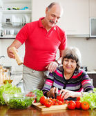Elderly couple cooking with tomatoes — Stock Photo