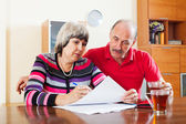 Mature couple fills in the questionnaire  — Stock Photo