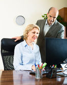 office scene with two elderly and positive workers — Stock Photo