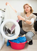 Housewife with  clothes near washing machine — Stock Photo