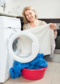 Housewife looking at  clothes near washing machine — Stock Photo