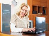 Femme mûre avec ordinateur portable à la table — Photo
