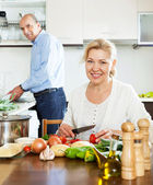 Ordinary mature couple cooking food with vegetables — Stock Photo