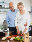 Loving elderly man and mature wife cooking vegetables — Stock Photo