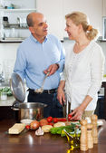Mature woman smiling and cook vegetables with loving senior — Stock Photo