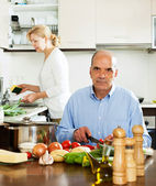 Mature man helping his wife in household work — Stock Photo