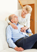 Happy mature woman with senior husband on sofa — Stock Photo