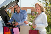 Man and woman putting bags  in car trunk — Stock Photo