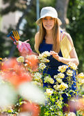 Smiling young female  in uniform at yard gardening — Stock Photo