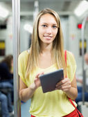 Female using ereader in subway — Stock Photo